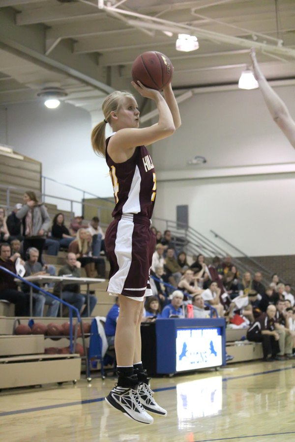Addie Lackey launches a three-point shot during the first half of Friday?s 55-50 overtime escape against Lyons. The Trojan senior scored 23 points in the game and is the team?s leading scorer at the holiday break with an average of 19.8 points per game.