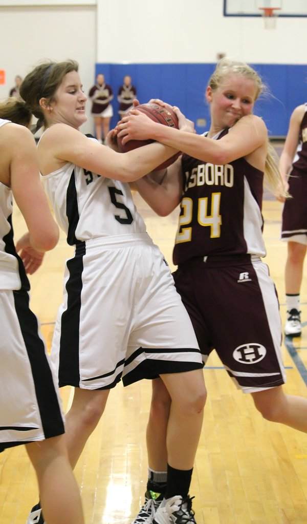 Addie Lackey ties up Sterling's Emma Lambert during a rebound scramble under the Trojan basket late in the first half.