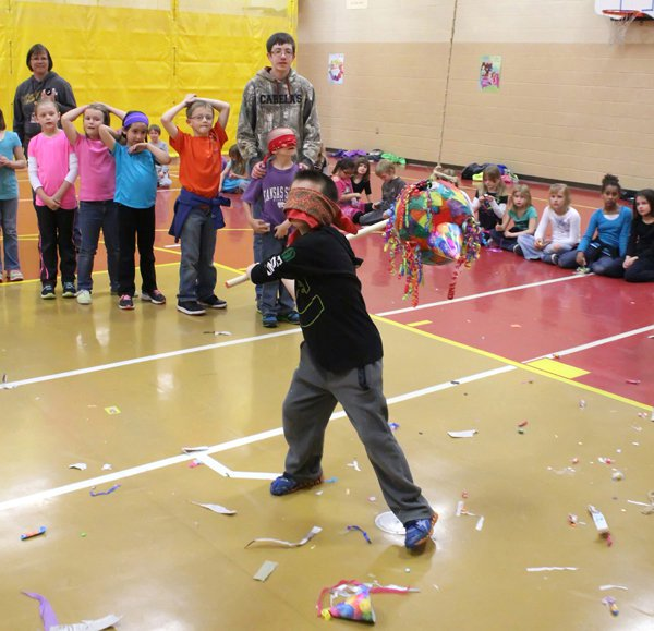 Romero Cruz takes a swing at a pinata while his classmates await their turn. Students from the high school Spanish class made 17 pinatas, and helped direct the event.