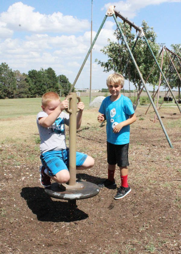 Second-grade classmates Colton Jost (left) and Jace VanWart play Monday afternoon on one of the spinners in the Hillsboro Elementary School playground. Most of the treated tree mulch has disintegrated or washed away.