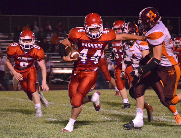 Adam Janzen extends the stiff arm on his way to the end zone for a 43-yard touchdown run during the first quarter that gave Marion an 18-0 lead over Herington. Marion won, 56-8.