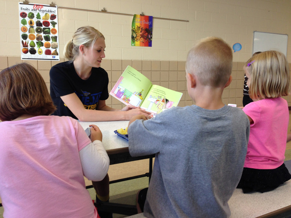 Amber Bonham, a freshman guard from Copan, Okla., shares a book with students. Tabor College photo