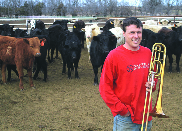 Derek Klingenberg hangs out with his trombone in the family?s cattle corral on their farm near Peabody. Wendy Nugent / Free Press