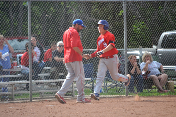 Peyton Heidebrecht rounds third base and is congratulated by coach Roger Schroeder after hitting a three-run home run during the top of the fifth inning of Game 1 at Little River Thursday. That gave Marion a 12-10 lead, and the Warriors went on to win the game, 15-11, after trailing by as much as 10-3. Janae Rempel / Free Press