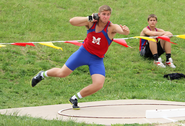 Senior Kyle Palic prepares to launch the shot put at the Hesston Invitational Thursday as freshman Tyler Palic observes. The elder Palic won the shot put with a throw of 48 feet, 41?2 inches. He also won the discus (158-7) and placed second in the javelin (140-8) to help lead the Marion boys to a second-place team finish with 83 points behind Hesston (110). Palic received the ?Outstanding Male Athlete Award? at the meet. Don Ratzlaff / Free Press