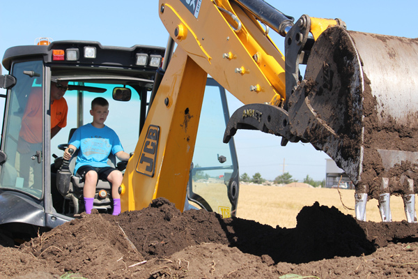 Landon Roberts prepares to scoop some compost dirt with the city?s back hoe during the third Hillsboro Youth Adventure.  Free Press Photos by Don Ratzlaff