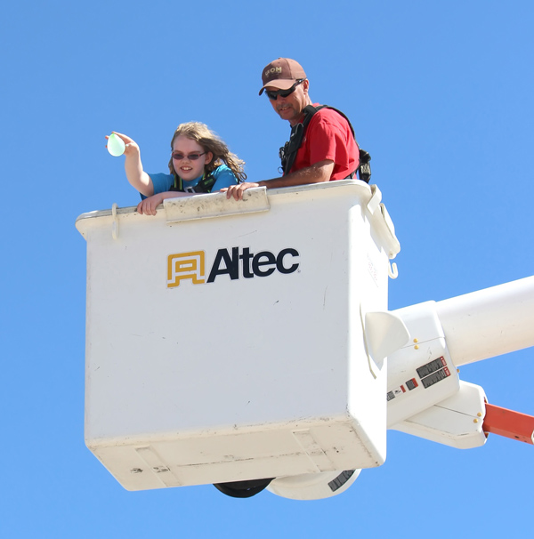 Olivia Jury is ready to drop a water ballon from the electric department bucket at a target 40 feet below her as Todd Helmer supervises. Free Press photos by Don Ratzlaff