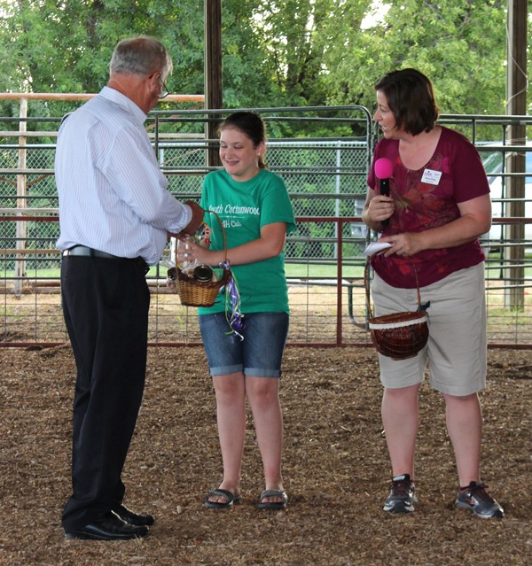 Ella Just of the South Cottonwood 4-H Club accepts the first prize for the Commissioners Cookie Jar contest. Presenting the basket of goodies is Dan Holub, commission chair. Renae Reidy, K-State Extension home economist, participated in the presentation. Courtesy photo