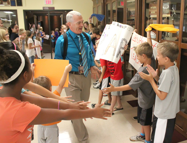 Hillsboro Elementary School principal Evan Yoder accepts the adulation of students and parents during a surprise ?pep rally? for all USD 410 staff members Monday morning. Don Ratzlaff / Free Press