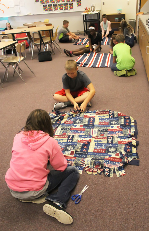 Don Ratzlaff / Free Press<p>Callie Bernhardt and Hunter Hein (foreground) work on their lap blanket featuring a variety of patriotic themes and messages.