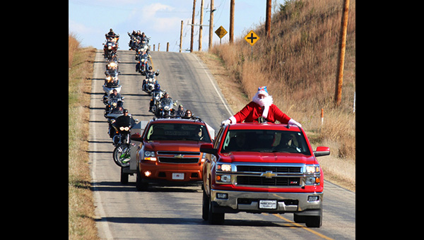 Don Ratzlaff / Free Press<p>Escorted by 131 motorcycles and 11 classic cars, Santa Claus rides a Chevy pickup down 190th Road from Marion to Hillsboro on Saturday afternoon. Event organizers are expecting more than $13,000 and many gifts for children in the county.