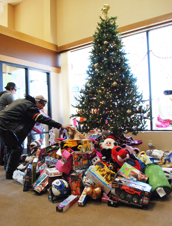 Patty Decker / Free Press<p>Toys contributed by Toy Run participants pile up around the Christmas tree at Hillsboro State Bank.