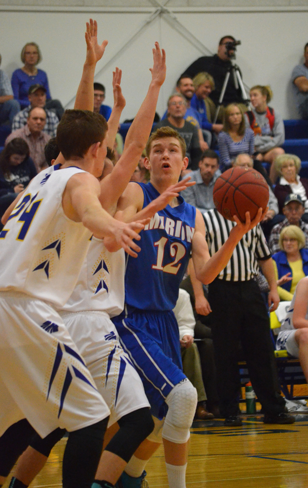 Zachary Stuchlik is guarded by two Berean Academy defenders during the first half of Tuesday's game. Marion lost the game, 61-37, to conclude the regular season.