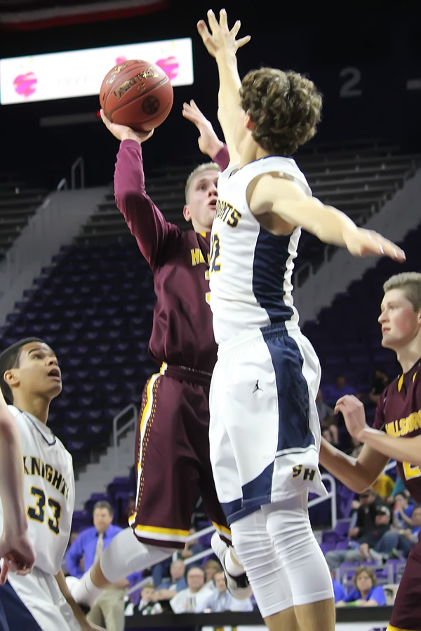 Darian Ratzlaff scores over Sacred Heart's Grant Herrenbruck during the second half of their first-round game. Ratzlaff scored 10 points during the contest.