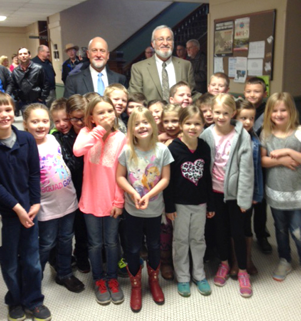 Students from Ginger Becker's first-grade class at Marion Elementary School swarm around Judge Michael Powers (standing, left) and Kent Becker, after watching their teacher's husband be sworn in as the new county commissioner for District 1 prior to Monday's meeting. He succeeds Lori Lalouette, who resigned.
