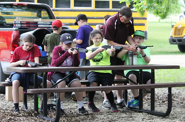 Teacher Len Coryea offers some pellet-gun shooting tips to Joshua Diener. Also seated at the shooting table are classmates (right to left) are Kori Arnold, Ashlyn Larabee and Karley Loewen.