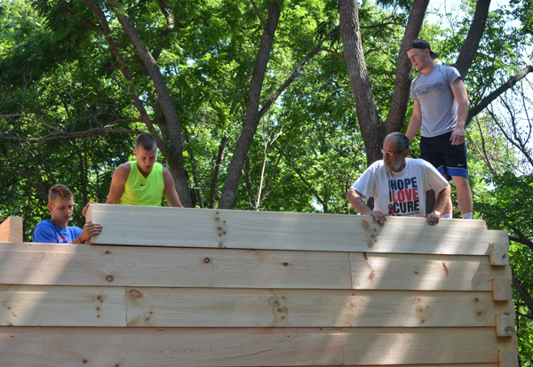 Zachary Stuchlik, Jack Schneider, Gerald Wiens and Corbin Wheeler secure a log around the joists for the cabin's loft. The three Marion High School seniors are helping Wiens build a log cabin in western Chase County.