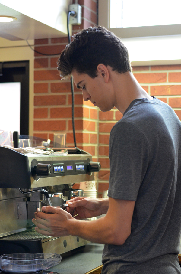 Austin Calam, one of three co-managers of Java Jays Coffee Bar, froths milk while making a lattemorning.