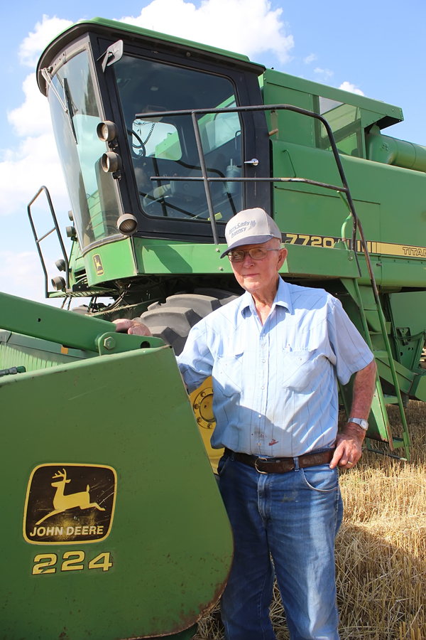 "Ed Hein poses with his John Deere 7720 before resuming the harvest effort on Wednesday. The 92-year-old Hein says, ""When it quits, I quit."""