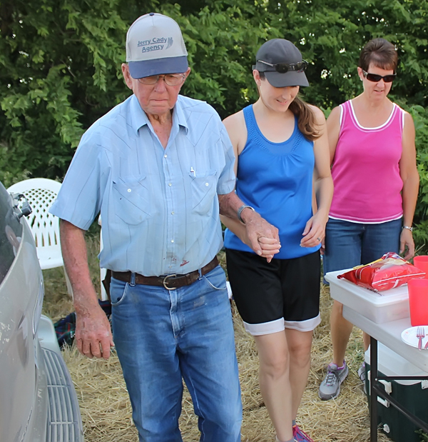 ">Ed Hein welcomes the steadying hand of granddaughter Staci Morales as he heads back to his combine. Morales is the designated truck driver for the Hein crew. Daughter-in-law Beth Hein (right) prepares to ""break camp."""
