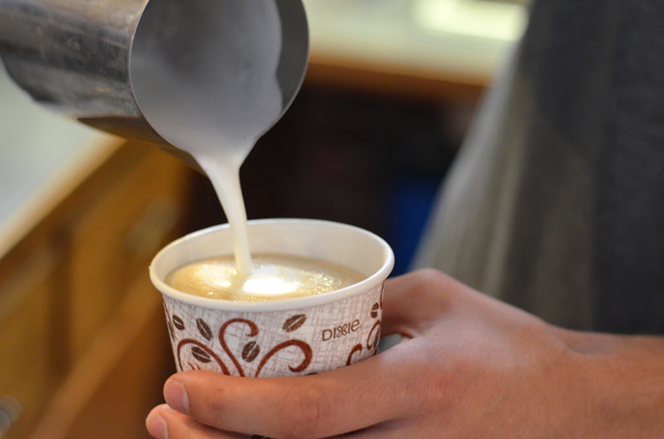 Austin Calam pours frothed milk over espresso to make latte art. All workers at Java Jays are trained to be able to pour latte art, Calam said.<p>