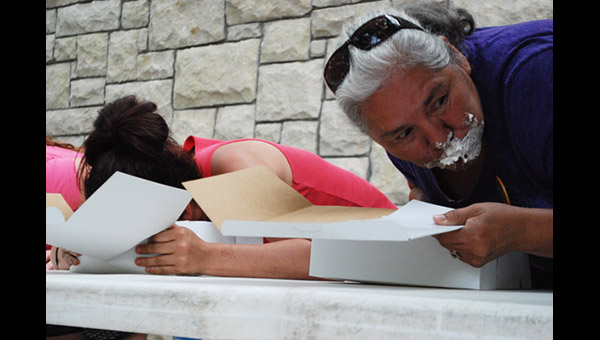Cindy Griffitts (far right), winner of the pie-eating contest sponsored by FamLee Bakery in Marion, glances to her left to check the progress of one of the 20 contestants on Saturday afternoon.