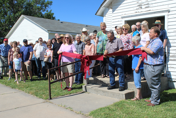 Board member Richard Dirks cuts the ceremonial ribbon in front of the Kreutziger School to officially open the exhibit.