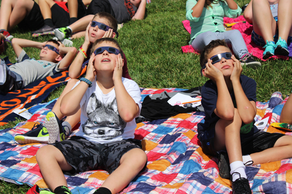 Fifth-graders (foreground) Jace VanWart (left), Emery Dalke (right) and classmate Luke Isaac (behind VanWart) gaze at the solar eclipse through protective glasses. Students tracked the eclipse by watching the sun for a few minutes at a time.