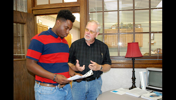 "Intern DiMitri Bowie and Marion City Administrator Roger Holter review a living document on a capital improvement project as part of Bowie's experience with Marion city government this summer. ""The internship program has been a real eye-opener,"" Bowie said. ""It takes so many things to run this city."""