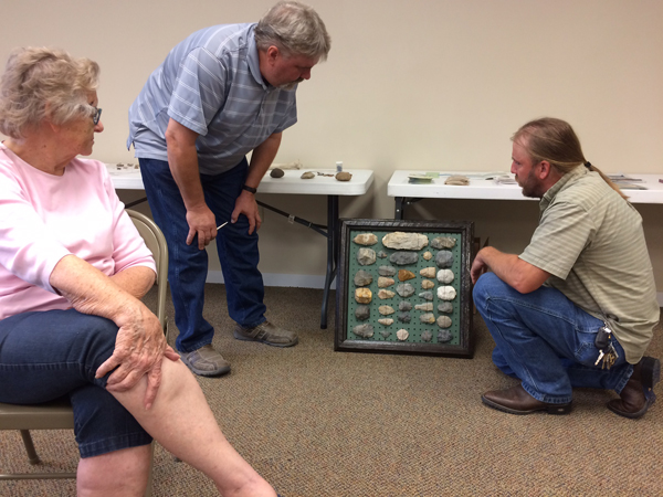 """Margie Reed, author of """"The Archaeology of Central Kansas,"""" which is based on the Reed collections from sites in Saline and Ottawa counties, listens as professional archaeologist Tod Bevitt (right) talks to Marty Fredrickson about one part of his collection during a workshop Saturday at the Marion City Library."""