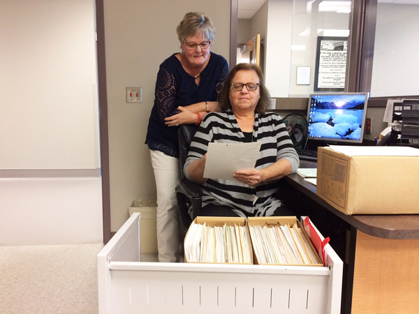 Hillsboro Community Hospital employees Kathy Ehrlich, records manager, standing, looks at one of the old documents Lillian Bookless, social services designee and transcriptionist, reviews. The two women are wanting to match the rightful parents with the unofficial copy of the birth certificate and footprints.