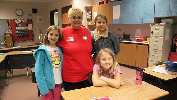 Diana Dalton poses with three of her student friends from Lenna Knoll's third-grade class at Hillsboro Elementary School. Dalton is the first participant in the Foster Grandparents program that the school is developing. Pictured with her are Allie Cardinell (left), Lydia Moser (seated) and Meladen Champion.