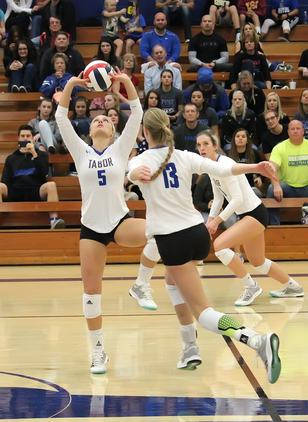 Tabor College setter Megan Voth positions the ball for an attack hit by Sydney Peitz during Saturday's opening-round NAIA win over Trinity Christian College.