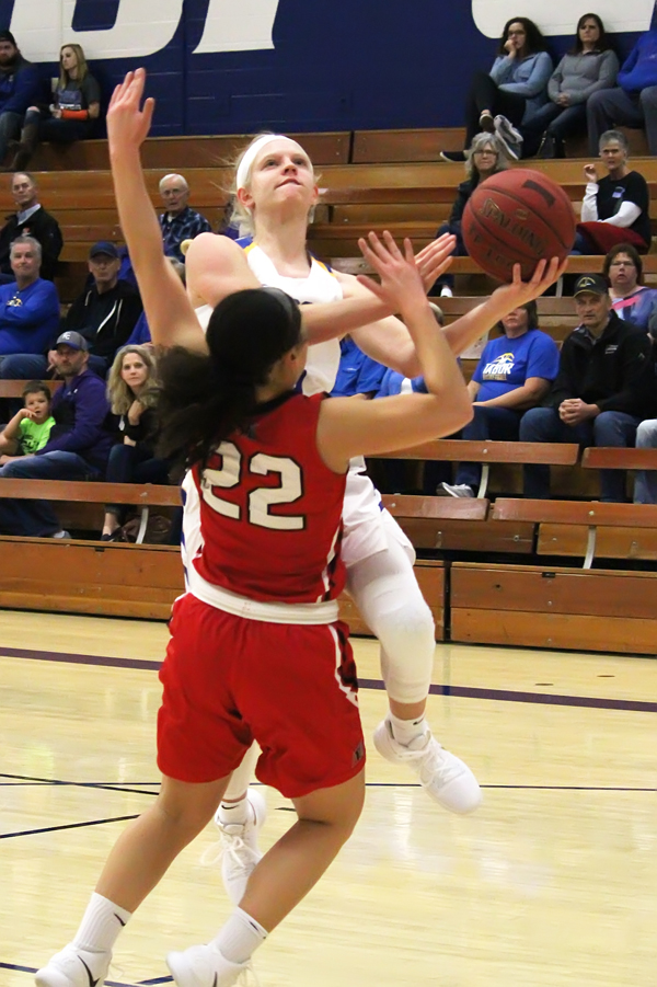 Tabor guard Morgan Ediger scores in the first half against McPherson's Brooklyn Coe on the way to 26 points for the game and a 68-49 Tabor victory.