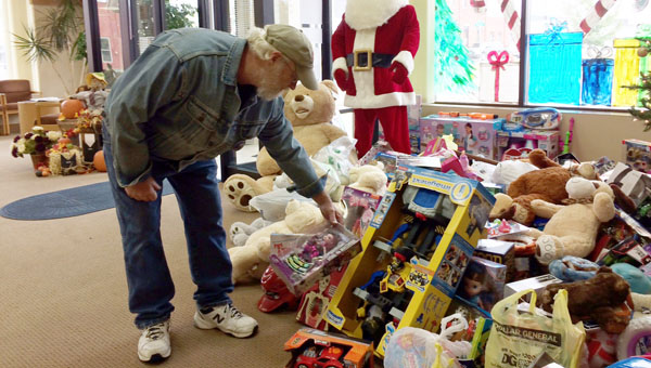 Kim Abrahams, one of the organizers of the Marion County Toy Run, looks over the toys that were collected at Hillsboro State Bank from those who rode their motorcycles and classic cars from Marion to Hillsboro on Saturday.