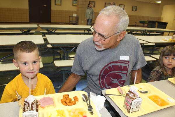 >Xavier Ratzlaff enjoys his meal with his grandfather, Glenn Ratzlaff.<p><p>