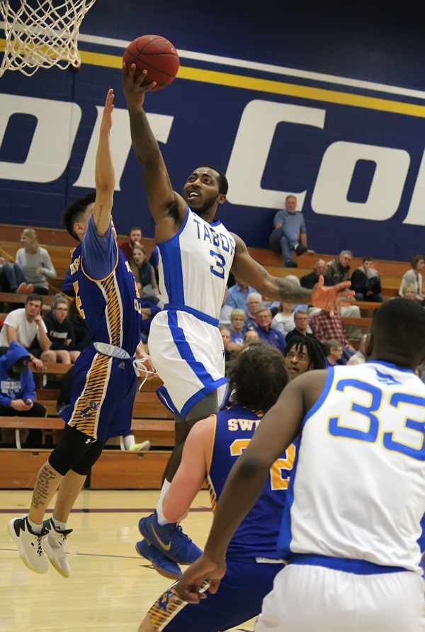 Tabor's guard DeShun Patterson scores in traffic during the second half of Tabor's 98-65 win over Bethany College on Saturday night. Patterson finished with eight points.
