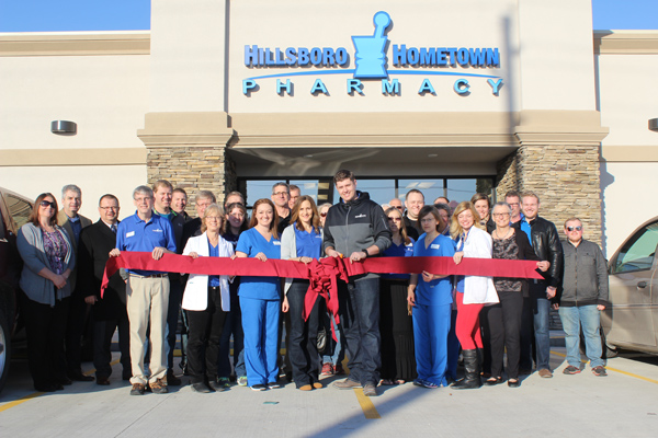 Hillsboro leaders and residents gathered with pharmacy staff for the ceremonial ribbon cutting at the new Hillsboro Hometown Pharmacy March 1. Owner Eric Driggers prepares to cut the ribbon.