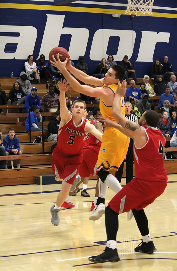 Gaven Schumann makes his move to the basket for two of his eight points in Tabor's 76-64 loss to Friends University on Saturday..