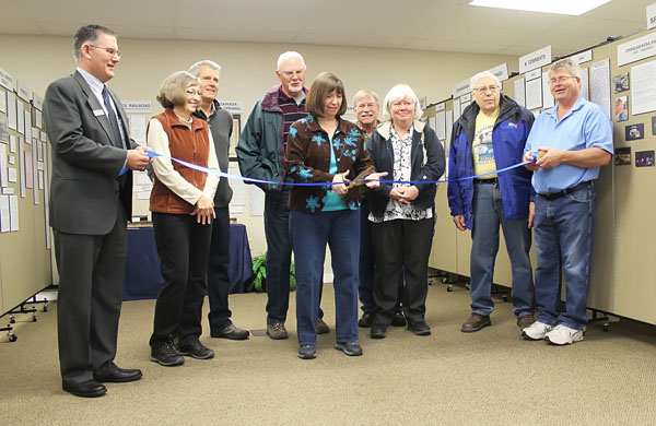 Surrounded by project supporters, Shari Padgham cuts the ribbon Saturday marking the opening of the month-long local exhibit.<p>