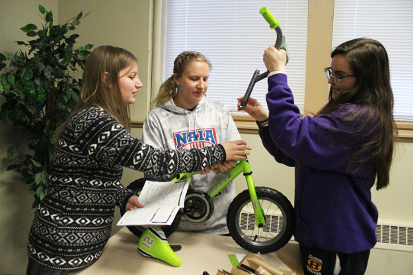 Future teachers are assembling a small bicycle using a direction manual. More than learning how to assemble a bicycle, the students are learning how to create excitement for learning.