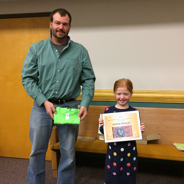 Damien Svitak, treasurer of the Marion County Conservation District Board of Supervisors, congratulates Anani Ensley of Marion for winning first place in this year's poster contest by depicting conservation efforts using watersheds, which are simply precipitation collectors.
