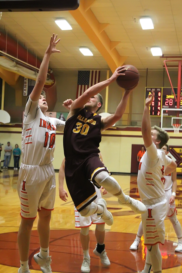 Hillsboro Darian Ratzlaff maneuvers between Inman's Mason Thiessen (left) and Jack Doerksen for two points in the second half of the sub-state finals. Ratzlaff scored 15 points to lead the Trojans in defeat. Thiessen, Inman's 6-foot-8 post scored 23 points in the Teuton's 53-49 victory.
