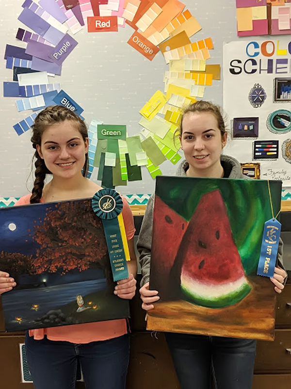 """Jenny Horne (left) features her oil painting that received the """"Student Choice Best of Show"""" ribbon as well as a yellow """"Merit Award"""" ribbon. The painting is of a girl sitting next to a lake on a fall night, lighting lotus flower lights and sending them off on the water. Dasha Elizabeth Brandt (right) holds her first-place ribbon for her oil painting, which is a still life of two slices of watermelon."""