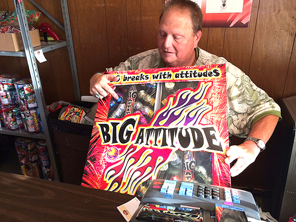 """Scott Zogelman, member of Florence PRIDE committee, shows one of the larger packages of fireworks called, """"Big Attitude."""" Free Press/Patty Decker"""
