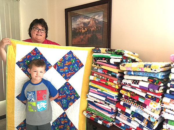 "Lana Hauschel, with 5-year-old grandson Easton, holds one of the 64 quilts pieced by her mother that will be donated to Project Linus for distribution to hospitalized children. ""They give quilts to sick and terminally children in the Wichita area hospitals, I believe,"" said Hauschel, adding that she intends to make an annual donation in her mother's honor. Free Press/Aleen Ratzlaff"
