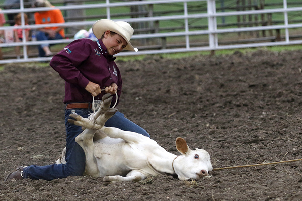 Mason Stueve ties three legs of a calf during the Tie Down competition at the rodeo at the Marion County Fair on Wednesday evening. Phyllis Richert/ Free Press