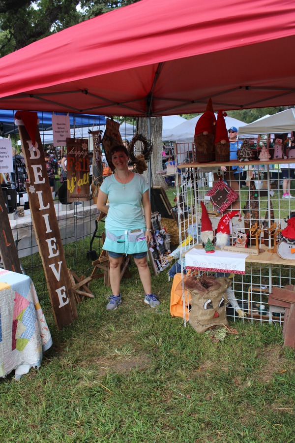 "Amy Plett stands at her booth at Art in the Park in Central Park in Marion. She sold festive, holiday wooden creations. ""I love having a booth at the Marion fair because it is much cooler being on grass than on the asphalt,"" said Plett. Laura Fowler Paulus/Free Press"