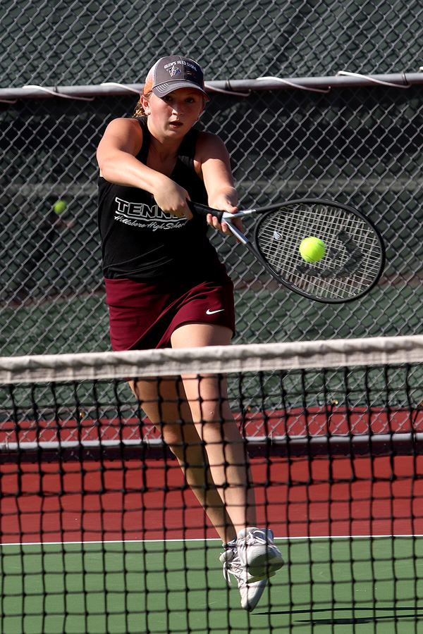 Cheyenne Bernhardt returns a serve during competition at the Hillsboro Invitational tennis meet on Tuesday. She and her doubles partner Kyla Isaac earned 2nd place in the #1 doubles division.