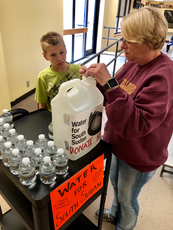 "Hillsboro students help- HMS student DJ Bartel is helped by staff member Terry Penner. DJ designed the water bottle labels for the fundraiser that the school is doing after reading the book ""A Long Walk to Water""."
